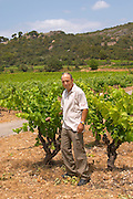 Sylvain Fadat Domaine d'Aupilhac. Montpeyroux. Languedoc. Vines trained in Gobelet pruning. Old, gnarled and twisting vine. Mourvedre grape vine variety. Chateau de Castellas ruin. Owner winemaker. France. Europe. Vineyard.