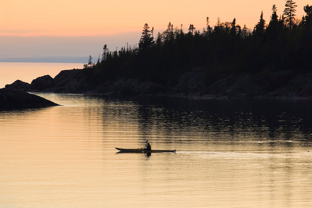 A sea kayaker is silhouetted as she paddles the calm waters of Chalfant Cove at dusk in Lake Superior Provincial Park near Wawa Ontario Canada.