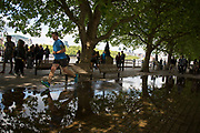 Man running through a deep puddle under trees after heavy rain on the riverside walkway. The South Bank is a significant arts and entertainment district, and home to an endless list of activities for Londoners, visitors and tourists alike.