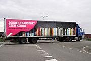 Nederland, Bemmel, 16-3-2020 Een vrachtwagen draait een weg op . Op de zijkant staat : zonder transport geen kennis en zonder transport staat alles stil . Een foto van een boekenkast is te zien . Foto: Flip Franssen