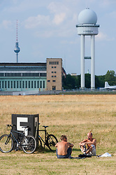 Men relaxing in public Tempelhofer  Park at former Tempelhof Airport in Berlin Germany