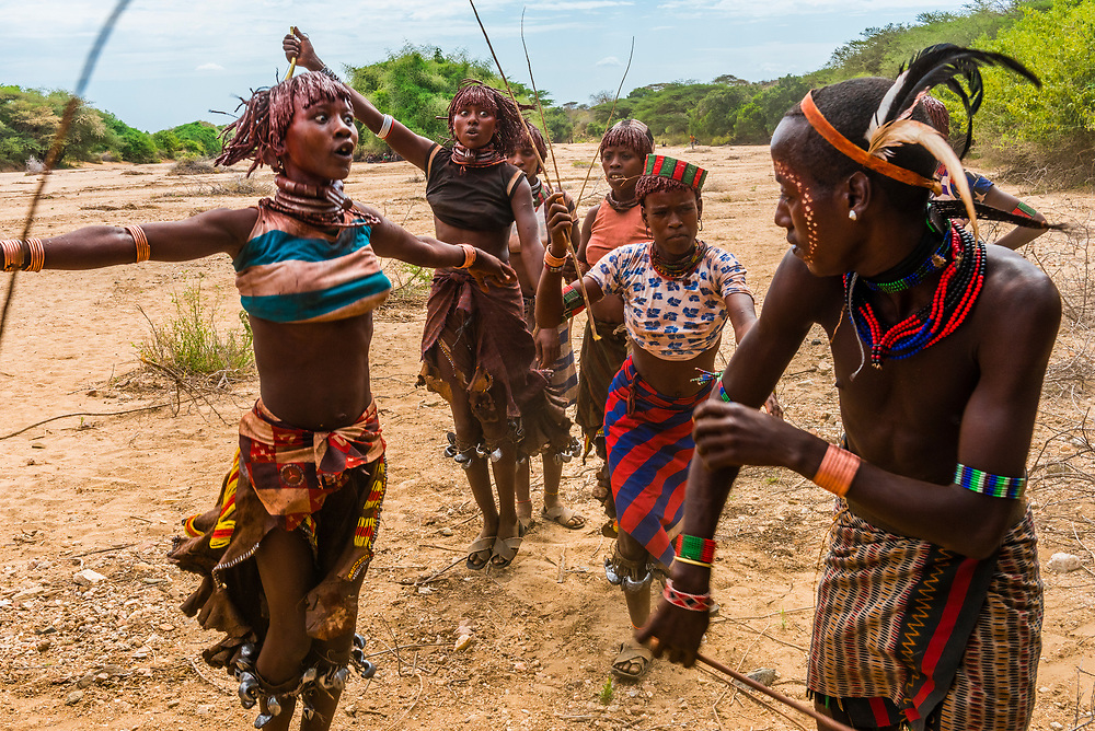 """At the Hamer tribe bull jumping ceremony, a rite of passage initiating a boy into manhood, women and girls beg the men to whip them. They are supposed to ask to get whipped and antagonize the """"maza"""" (who has already gone through the ceremony previously, to hit them harder. Deeper scars show higher intensities of commitment to the men.  Omo Valley, Ethiopia."""