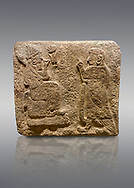 Alaca Hoyuk Sphinx Gate Hittite monumental relief sculpted orthostat stone panel. Andesite, Alaca, Corum, 1399 - 1301 B.C. Anatolian Civilisations Museum, Ankara, Turkey.<br /> <br /> Figure with a sharp and horned headdress (probably a god) sitting on a stool with a short backrest, with a figure (probably the figure of a king) worshipping to it. Both figures wear a large and ring-shaped earring. Among them is a hieroglyph, the symbol of divinity.<br /> <br /> Against a brown gray background. .<br />  <br /> If you prefer to buy from our ALAMY STOCK LIBRARY page at https://www.alamy.com/portfolio/paul-williams-funkystock/hittite-art-antiquities.html . Type - Aalca Hoyuk - in LOWER SEARCH WITHIN GALLERY box. Refine search by adding background colour, place, museum etc.<br /> <br /> Visit our HITTITE PHOTO COLLECTIONS for more photos to download or buy as wall art prints https://funkystock.photoshelter.com/gallery-collection/The-Hittites-Art-Artefacts-Antiquities-Historic-Sites-Pictures-Images-of/C0000NUBSMhSc3Oo