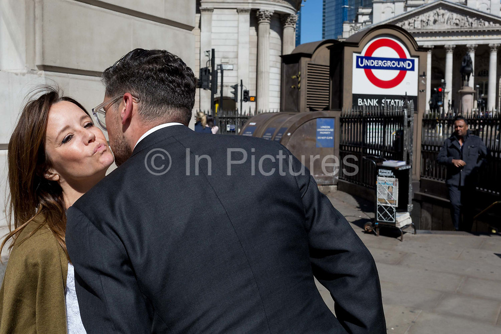 A man and woman say goodbye outside one entrance of Bank Underground Station in the City of London, the capitals ancient, financial district, on 14th May, in London, England.