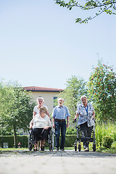 Senior man and women with mobility walker and wheelchair at garden footpath, Bavaria, Germany, Europe