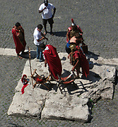 Tourists at the Roman Collosseum (also known as the Flavian Amphitheatre), an elliptical amphitheatre in the centre of Rome, Italy. Considered one of the greatest works of Roman architecture and engineering. Built from concrete and stone, with construction starting under the emperor Vespasian in 70 AD, finished in 80 AD under Titus. The amphitheatre also underwent modifications during the reign of Domitian. Named for its association with the Flavius family name of which these 3 emperors belonged. The Collosseum seated 50,000 spectators to view gladiatorial contests and performances. It was later repurposed for many other uses. One of the outstanding physical representations of Imperial Rome.