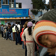 Fans queue up outside El Alto's Multifunctional Centre waiting to watch the 'Titans of the Ring' wrestling group who perform each Sunday at El Alto's Multifunctional Centre. Bolivia. The wrestling group includes the fighting Cholitas, a group of Indigenous Female Lucha Libra wrestlers who fight the men as well as each other for just a few dollars appearance money. El Alto, Bolivia, 17th January 2010. Photo Tim Clayton