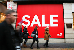 "© Licensed to London News Pictures. 23/12/2018. London, UK. Shoppers walk past H&M store with a window displaying ""SLAE"". Last minute Christmas shoppers take advantage of pre-Christmas bargains in London's Oxford Street. Fewer shoppers have been reported shopping in Britain's high streets as online sales increase. Photo credit: Dinendra Haria/LNP"