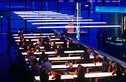 A young couple sit at a bench for an intense and intimate talk in the London Science Museum's Deep Blue Cafe. With illumination coming from overhead strip lighting and from below, inside the tables, people sit at the long seating to enjoy the food and drink sold by the Science Museum. The family restaurant, located on the ground floor at the back of the museum serves meals prepared on the premises using fresh, carefully sourced ingredients. A great place to relax and refresh with great views of the high-tech Wellcome Wing.