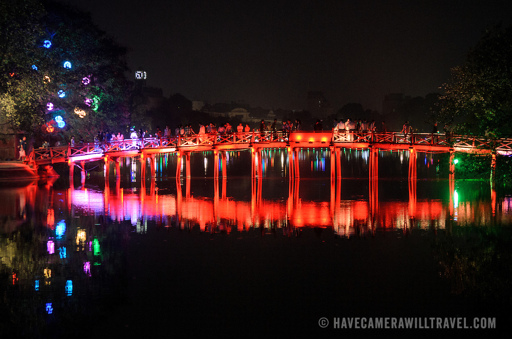 View of The Huc Bridge (Morning Sunlight Bridge) from the northern shore of Hoan Kiem Lake at night. The red-painted, wooden bridge joins the northern shore of the lake with Jade Island and the Temple of the Jade Mountain (Ngoc Son Temple).