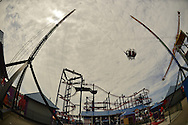 Brooklyn, New York, USA. 10th August 2013. The Sling Shot ride carries two riders high in the cloudy sky, with the Soarin' Eagle ride twisting tracks seen behind it and the Zenobio ride to the extreme right, at the 3rd Annual Coney Island History Day celebration. Taken with 180 degree fisheye lens.