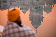 "A Sikh pilgrim sits in silence and reflection  at the edge of the Amritsagar, the pond that surrounds the Golden Temple, Sikhisms' holiest of ""Gudwaras"", Amritsar, Punjab, India"