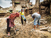 04 AUGUST 2015 - KHOKANA, NEPAL: Homeowners remove earthquake debris from the street in front of their home in Khokana, a village about an hour from Kathmandu. Three months after the earthquake, roads in many rural villages are still blocked by earthquake debris. The Nepal Earthquake on April 25, 2015, (also known as the Gorkha earthquake) killed more than 9,000 people and injured more than 23,000. It had a magnitude of 7.8. The epicenter was east of the district of Lamjung, and its hypocenter was at a depth of approximately 15 km (9.3 mi). It was the worst natural disaster to strike Nepal since the 1934 Nepal–Bihar earthquake. The earthquake triggered an avalanche on Mount Everest, killing at least 19. The earthquake also set off an avalanche in the Langtang valley, where 250 people were reported missing. Hundreds of thousands of people were made homeless with entire villages flattened across many districts of the country. Centuries-old buildings were destroyed at UNESCO World Heritage sites in the Kathmandu Valley, including some at the Kathmandu Durbar Square, the Patan Durbar Squar, the Bhaktapur Durbar Square, the Changu Narayan Temple and the Swayambhunath Stupa. Geophysicists and other experts had warned for decades that Nepal was vulnerable to a deadly earthquake, particularly because of its geology, urbanization, and architecture.     PHOTO BY JACK KURTZ