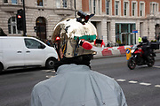 Female cyclist wearing a gold safety helmet with safety lights attached in London, England, United Kingdom. A bicycle helmet is designed to attenuate impacts to the head of a cyclist in falls while minimizing side effects such as interference with peripheral vision.