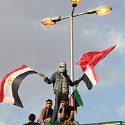 A youth climbs high over Cairo's Tahrir Square to wave his flags in support of continuing the Egyptian revolution.