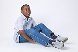 Young boy sitting on the floor smiling,