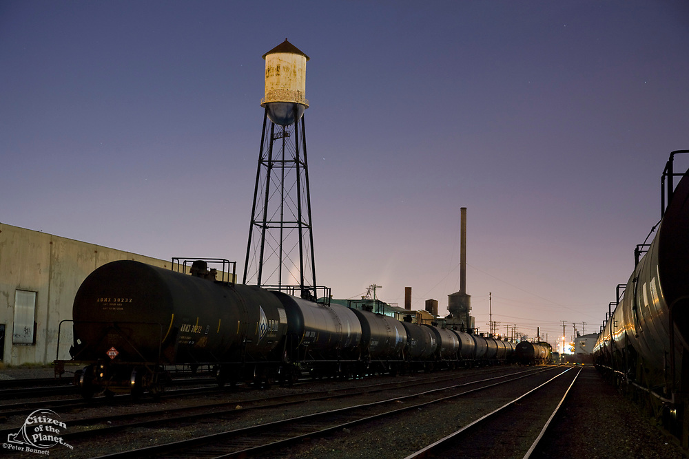 """Old Water tower in train yards in Vernon illuminated by moonlight. Located just a few miles from downtown Los Angeles, Vernon's official slogan is """"Exclusively Industrial"""" and at the last census had a population of 91. Los Angeles, California, USA"""