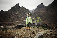 A little ethnic girl stands on a road side amidst the mountainous landscape of Ha Giang province, Vietnam, Southeast Asia