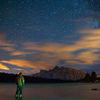 A camper watches he Milky Way soaring over Mount Rundle and Two Jack Lake in Banff National Park, Alberta, Canada.  The clouds are lit by lights from Calgary, Banff and the Trans-Canada Highway.
