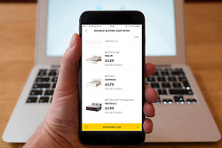 Using iPhone smartphone to display beds for sale in IKEA online home furnishing superstore