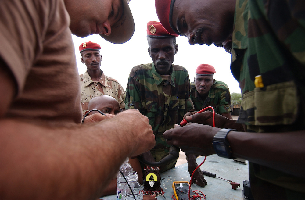 """ARTA, Djibouti -- March 25, 2006 -- U.S. Navy Construction Mechanic 1st Class David Borkowski, left foreground, works with Djiboutian Army Sgt. Farah Hassan Boueh to test the resistance in an ignition relay wire.  Borkowski, Leading Petty Officer of the Naval Mobile Construction Battalion 7's Engine Repair Department at Camp Lemonier, is teaching a two-week class on auto maintenance skills to the Djiboutian military at their camp in Arta. .Borkowski said, """"We're having to pull out every part, trouble check it and put it back in. This process assures us that the problems we're seeing are not the result of bad parts. It also has the added effect of teaching these guys how the whole engine goes together."""""""