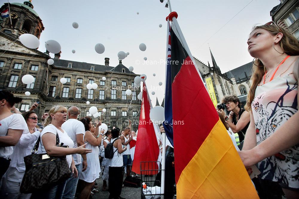 Nederland, Amsterdam , 23 juli 2014.<br /> Duizenden mensen lopen mee met een stille tocht door het centrum van Amsterdam. Volgens de organisatie zijn er zo'n vijfduizend deelnemers, meldt persbureau Novum. De wandeling begon om 20.00 uur op de Dam en eindigt daar ook weer. Deelnemers zullen daar witte ballonnen oplaten. Ook dragen zij witte kleding.<br /> Op de foto: Op de Dam wordt stil gestaan bij de verongelukte mensen van vlucht MH17 boven de Oekraine.<br /> Thousands of people in white clothes walk along with a silent march through the center of Amsterdam. The victims of flight MH17 are thus commemorated. National day of Mourning .