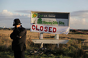 The sign for Shell Haven Oil Site defaced with green paint. An oil tanker can be seen in the back ground behind the depondend police officer.<br /> <br /> Crude Oil Awakening is a coalition of climate change activist groups. On Saturday Oct 16 they shut the only entrance to Coryton oil refinery in Essex, UK with the aim of highlighting the issues of climate change and the burning of fossil fuels. The blockade meant that a great number of trucks with oil were not able to leave the refinary during the day of action.
