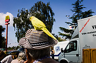 Waterloo Belgium 2017 13 Augustus marche au puces. Man with a yellow parrot on his hat with mac donalds logo in the background