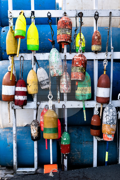 Colorful lobster trap floats hang on a wall at a wharf in the tiny fishing community of New Harbor, Maine. The picturesque pocket harbor is one of the last working harbors on the midcoast along the Pemaquid Peninsula