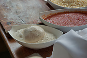 Preparing and baking a focaccia pizza with tomato puree and cheese