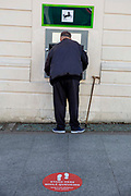 An elderly man with a walking stick withdraws cash from a Lloyds bank ATM machine in front of  the 2 metre social distancing advice stuck to the floor outside Lloyds bank on the 15th of June 2020 in Folkestone, United Kingdom.