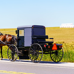 Gordonville, PA, USA / June 8, 2020: An usual configured Amish buggy includes outside benches travels along a rural road Lancaster County.