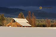 Days last light on snowy barn in Whitefish, Montana, USA