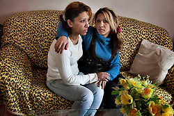 "Denisa Holubova sits with her daughter of the same name in their home in Ostrava, Czech Republic on March 4, 2012. The younger Denisa was one of 18 Roma children who were represented in the D.H. and Others v. Czech Republic case, the first challenge to systemic racial segregation in education to reach the European Court of Human Rights. When this case was first brought in 2000, Roma children in the Czech Republic were 27 times more likely to be placed in ""special schools,"" intended for the mentally disabled, than non-Roma children. In 2007, the Grand Chamber of the European Court of Human Rights ruled that this pattern of segregation violated nondiscrimination protections in the European Convention on Human Rights. Despite this landmark decision, little change has occurred: the ""special schools"" have been renamed but follow the same substandard curriculum and Roma continue to be assigned to these schools in disproportionate numbers. The process of integration has barely begun."