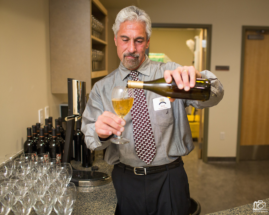Mark Capalongan, owner of Big Dog Vineyards, pours a glass of wine during during the City of Milpitas 60th Anniversary Gala at Milpitas City Hall in Milpitas, California, on January 25, 2014. (Stan Olszewski/SOSKIphoto)