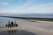 A family of three sit on the edge of a saltwater pool at Clevedon, on 22nd April 2017, in North Somerset, England.