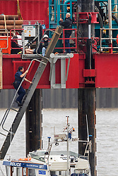 © Licensed to London News Pictures. 25/07/2020. London, UK. River Police climb onto a drilling rig in the Thames close to the 02 Arena in Greenwich which three Extinction Rebellion activists locked on to earlier this morning. The rig is involved with preparatory drilling for the Silvertown Tunnel which is planned to connect the Greenwich Peninsula with west Silvertown. Extinction Rebellion oppose the building of the tunnel due to the increase air pollution it may cause. Photo credit: George Cracknell Wright/LNP