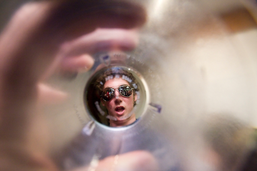Portrait of a college student wearing aviator sunglasses at a party in Stanford, California, as seen through a plastic drinking cup.