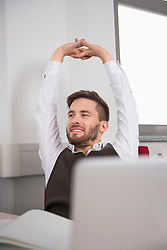 Young man relaxing office outstretched arms