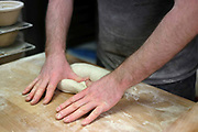 A baker kneading sourdough bread at the Haxby Bakehouse, Yorks artisan bakery in Haxby, North Yorkshire, United Kingdom on 10th February 2017. Haxby Bakehouse make bread using traditional methods of slow fermentation. They use low yeasted overnight sponges, natural sourdough levain or a combination of the two. This means the bread they produce is full of flavour without the use of any artificial flour improvers, preservatives or emulsifiers.