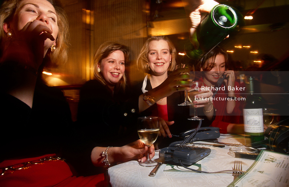 More wine is flowing from a bottle being poured from an anonymous hand during a phone speed-dating night in a City of London wine bar, a group of young girls enjoy white wine, their girlfriends' company but also, the possibility of finding a male mate. With the boys an other tables whose numbers are swapped around they may find the love of their lives although the whole evening is a giggle for these pretty lady office workers in the capital's oldest quarter and heart of its financial district.