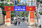 Gateway to lane, showing international Communist Party hammer and sickle and Vietnamese flag. Vung Tau, Vietnam