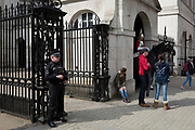 An armed police officer stands guard at Horseguards on Whitehall, in the aftermath of the terrorist attacks a week earlier, on 28th March, 2017, in London, England.