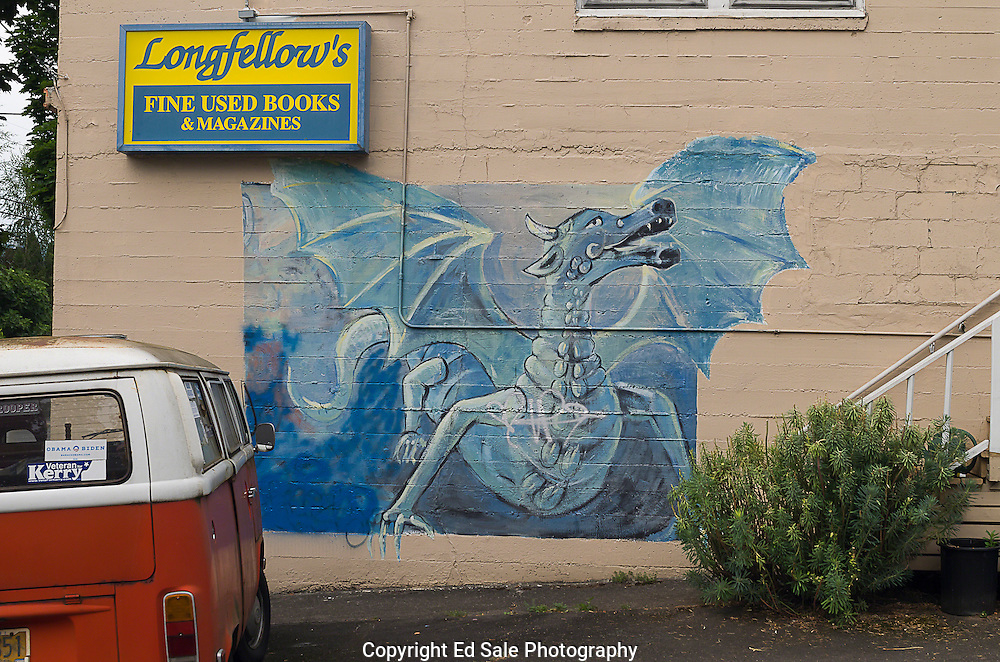 A colorful mural of a blue dragon painted on an exterior building wall in S.E. Portland, Oregon is framed by a Volkswagen bus and a business sign.