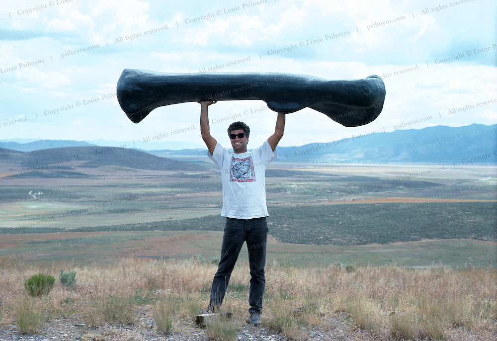 Author of Hunting Dinosaurs, Louie Psihoyos holds up a fiberglass cast of an Ultrasaurus femur near Provo Utah.