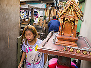 29 MARCH 2013 - BANGKOK, THAILAND:  People go by a spirit house in the Klong Toey slum. Spirit houses are a traditional part of Theravada Buddhist culture and is way of honoring one's ancestors.    PHOTO BY JACK KURTZ