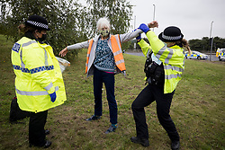 © Licensed to London News Pictures. 20/09/2021. Welwyn Garden City, UK. An elderly protester being arrested. Protesters from Insulate Britain attempt to blockade the A1M junction 4 near Welwyn Garden City, Hertfordshire. Climate change activists Environmental protest group Insulate Britain have successfully blocked traffic at various points of the M25 on several occasions over the past week. Photo credit: Ben Cawthra/LNP