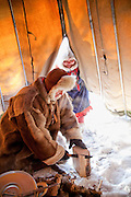 A Sami man and woman build a fire in a lavvu, a traditional temporary tent, in Karasjok, Finnmark region, northern Norway