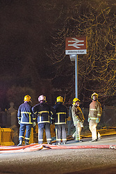 © Licensed to London News Pictures . 13/03/2013 . Alderley Edge , Cheshire , UK . Fire crew stand by the adjacent Alderley Edge railway station . Famous celebrity nightclub , Panacea , in Alderley Edge , is ablaze tonight (12th March) . Fire crews and police were initially called to the venue at 22:30 on Tuesday night (12th March) . Around 50 fire-fighters from Cheshire and Greater Manchester worked to control the fire at the venue , which is adjacent to a petrol station and residential properties in the affluent village of Alderley Edge . This is the second time in five years the venue has been destroyed by fire , previously following a £3.2 million refurbishment in September 2008 . Photo credit : Joel Goodman/LNP