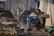 Los Angeles, California, U.S. - <br /> <br /> Life On The Edge<br /> <br /> According to the Los Angeles Homeless Services Authority, the homeless population of Los Angeles and L.A. County has increased as much as 20% in the last year, and leads the nation in homeless unsheltered living, at nearly 70%.<br /> Homelessness here has grown substantially since the last El Niño, which dumped 30 inches of rain on Los Angeles during the winter of 1997-98, authorities say. Recently, the Los Angeles City Council declared a state of emergency on homelessness and called for $100 million to help address the growing crisis. The Los Angeles River flows through Los Angeles County, from Canoga Park in the western end of the San Fernando Valley, nearly 48 miles southeast to its mouth in Long Beach. Homeless people live along much of its length, with many located generally east of Downtown L.A., making their homes in and around the river, under overpasses or alongside rail lines and industrial wastelands. Those people - many dealing with disability, mental health and criminal justice issues - living in tents, improvised shelters and live-in vehicles, have increased 85% in the same period. Causes include high unemployment, low wages and escalating rents, coupled with gentrification and elimination of SRO hotels and cheap rooms, a last option for many. An estimated 800 people live in LA's riverbeds and storm drains, which will be deluged with powerful torrents when El Niño storms arrive in early 2016. Although the Sheriff's Department and LA's Homeless Services Authority have made numerous visits to warn residents, many see no compelling reason - or options - for moving. Most are not the transient homeless we are used to seeing but have set up semi-permanent living quarters in the LA River, which with its sweeping concrete vistas and city skyline sunsets may soon become both a beautiful and dangerous place to call home.<br /> <br /> One of several people living under the rails at Washington Street and the L.A. River <br /> ©